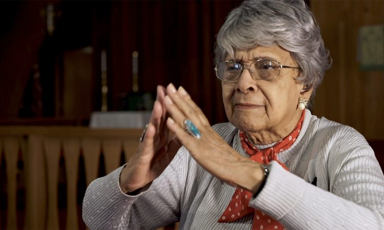 storyteller uses hands to imitate prayer and chapel architecture