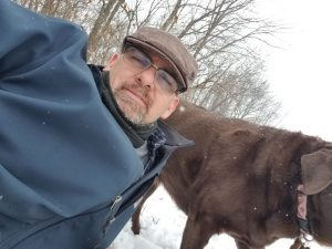 man wearing a cap with brown dog