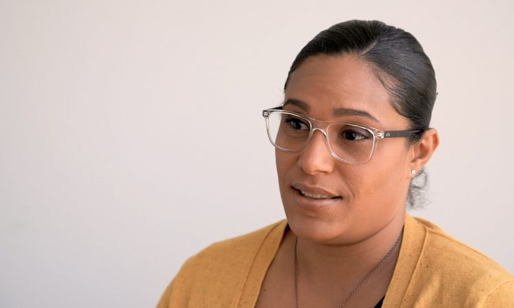 Woman with glasses and a yellow cardigan