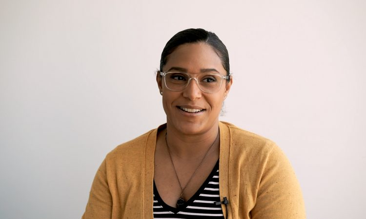 smiling woman with glasses and yellow cardigan