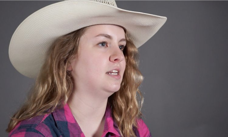 young woman with long hair wearing a cowboy hat